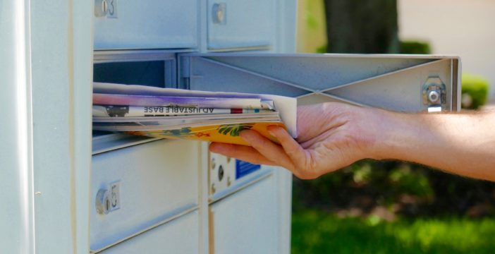 person colecting mail from post box