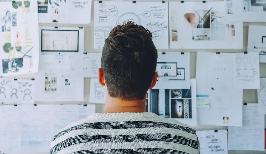 Man looking at ideas on wall
