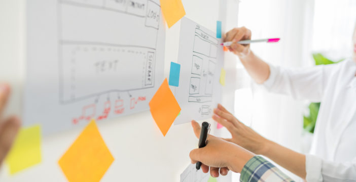 UX writers outline user flows and copy ideas on a whiteboard.